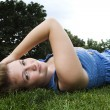 Beautiful girl laying down in park — Stock Photo