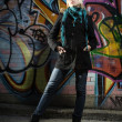 Woman standing in front of graffiti wall — Stock Photo