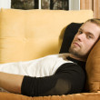 Young man laying on couch in living room — Stock Photo #5852354
