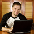 Stock Photo: Young male on laptop smiling