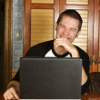 Young man laughing hysterically sitting at computer — Stock Photo