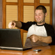 Happy man pointing at computer screen - Stock Photo
