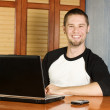 Very happy man sitting at computer — Stock Photo
