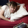 Grumpy young man waking up - Stock Photo