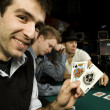 Young poker player holding winning hand — Stockfoto