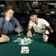 Four friends around table playing poker — Stock Photo