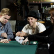 Stock Photo: Playing poker around table