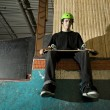 Skateboarder sitting on ramp — Stock Photo #5852636