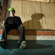 Skateboarder sitting on ramp - Stock Photo