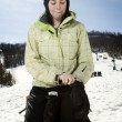 Beautful girl at ski hill putting on her gloves - Stockfoto