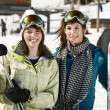 Two beautiful girls holding there skis — Stock Photo