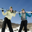 Two young girls holding there skis in the air — Stock Photo