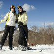 Two young girls on mountain top skiing — Stock Photo