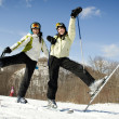 Two sisters on mountain top excited to be skiing - Stock Photo