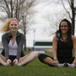 Two young women stretching in park before jog — Stock Photo