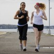 Two young women jogging together — Stock Photo