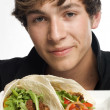 Young man holding up plate of tacos - Stock Photo