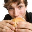 Young man eating his sloppy burger — Stock Photo