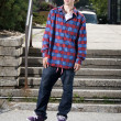 Fashionable skateboarder standing on board — Stock Photo