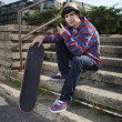 Teenage skateboarder sitting on stairs — Stock Photo #5853249