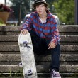 Teenage skateboarder sitting on stairs — Stock Photo #5853250