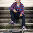 Skateboarder sitting down smiling for camera — Stock Photo #5853253