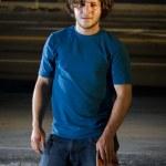Skateboarder standing in underground parking lot — Stock Photo #5853323