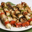 Barbequed kebabs on white plate — Stock Photo