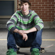 Stock Photo: Skateboarder sitting on board