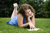 Girl reading book in grass — Stock Photo