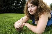 Girl making wish in grass — Stock Photo