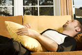 Young man sleeping on couch in living room — Stock Photo