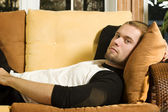 Young man laying on couch in living room — Stock Photo