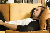 Young man having a nap on couch in living room — Stock Photo
