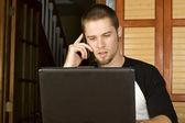 Varón joven hablando por teléfono mientras que en equipo — Foto de Stock