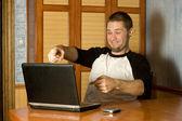 Happy man pointing at computer screen — Stock Photo