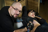 Tattoo artist tattooing happy client — Stock Photo