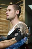 Man getting tattooed on arm — Stock Photo
