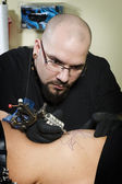 Tattooing on the side of clients abdomen — Stock Photo