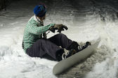 Snowboarder sitting in snow — Foto Stock