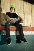 Młody skater siedzi na ziemi — Zdjęcie stockowe