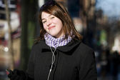 Woman on street listening to her MP3 player — Stock Photo