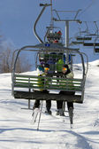 Two young girls on chairlift — Stock Photo