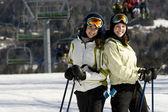 Two beautiful girls skiing together — Stock Photo