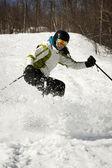Girl skier stopping on slope — Stock Photo