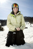 Beautful girl at ski hill putting on her gloves — Stock Photo