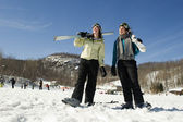 Two girl skiers looking up towards mountain — Stock Photo