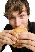 Young man eating his sloppy burger — Stock Photo