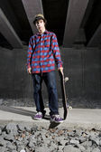 Skateboarder standing on path holding board — Stock Photo