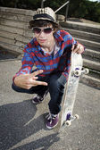 Skateboarder crouching down making peace sign — Stock Photo